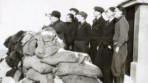 En svartvit bild på flera män, som blickar mot himlen efter bombplan.