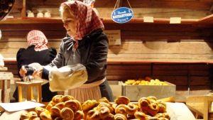 Tyttö myy sahramipullia Skansenilla
