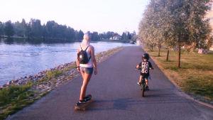 Äiti ja pieni poika yhdessä merenrantatiellä. Vaaleahiuksinen äiti kulkee skeittilaudalla ja kypäräpäinen poika pyöree vierellä polkupyörää.