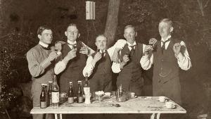 Fem män höjer sina snapsglas ute i en trädgård stående vid ett trädgårdsbord med kaffekoppar och flaskor