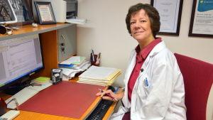 Läkare Leena Furubacka sitter vid sin dator i arbtesrummet