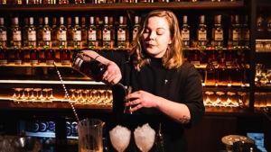 En bartender står vid en bar och häller upp två drinkar.