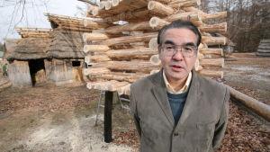 En medelålders man står framför träbyggnader med händerna bakom ryggen.