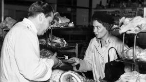 Kvinna köper kött med en ransoneringskupong i butik.