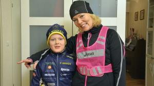 Katarina Liljeqvist och hennes son står klädda i träningskläder i hallen
