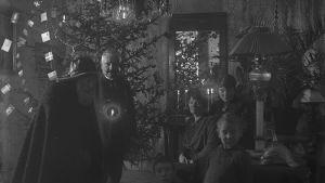 Julbocken på besök hos familj i vardagsrum med upplyst julgran
