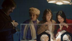 Rollfigurer i filmen Näkemiin Neuvostoliitto hänger över en kuvös i en dämpad sjukhussal.