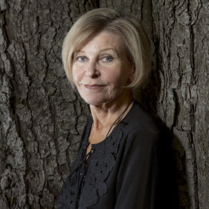 Elina Reenkola katsoo kameraan nojaten puuhun.