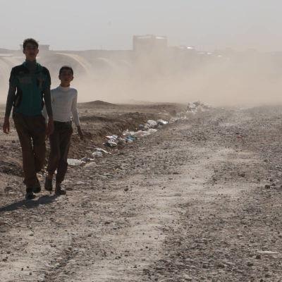pojkar i dammet på flyktingläger utanför Mosul