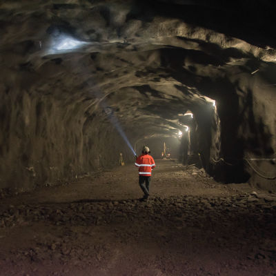 En byggarbetare lyser med ficklampa på betonglagret som täcker en ny metrotunnel i Esbo.