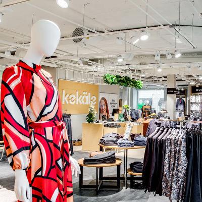 Mallinukke seisoo värikkäässä mekossa uuden vaatemyymälässä.