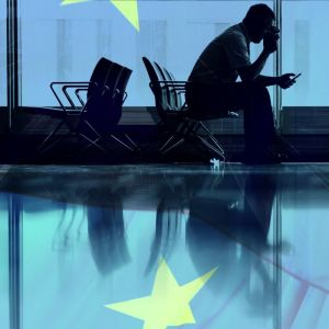 Mies katso puhelinta lentoasemalla