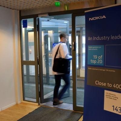 Työtekijä kulkee Nokian Oulun tehtaan ovista Ruskossa.