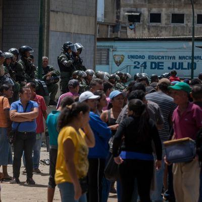 Ihmisjoukko seisoskelee takanaan mellakkavarusteisii pukeutuneita poliiseja.