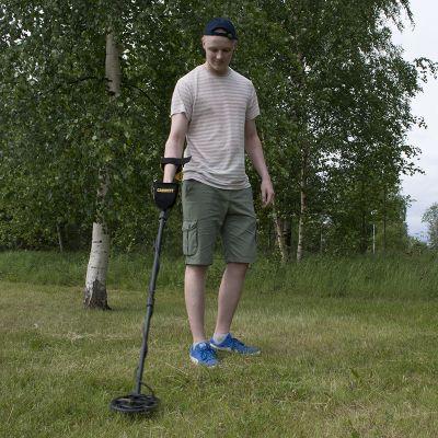 Alex Anttila käy nurmialuetta läpi metallinpaljastimella.