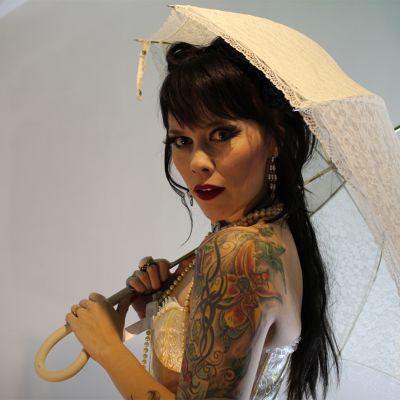 Burleskiesiintyjä Tanja Karppi poseeraa esiintymisasussaan päivänvarjon kanssa.