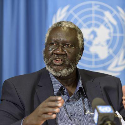 Harmaa hiuksinen, silmälasipäinen mies tummassa puhuu mikrofonin edessä, taustalla sininen verho, jossa näkyy YK:n logo.