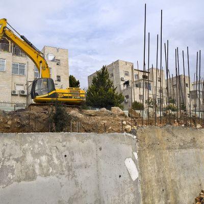Kuormakaivuri kerrostalojen edessä, kuvan edustalla betoni rakenteita, joista sojottaa metallitankoja.