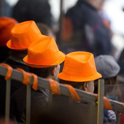 Kolme miestä oranssissa hatuissa jääkiekkokatsomossa