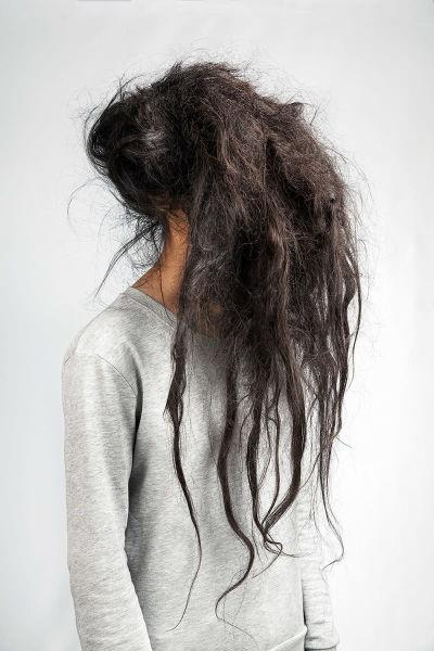 En kvinna i grå tröja. Ansiktet täcks helt och hållet av hennes långa svarta hår.