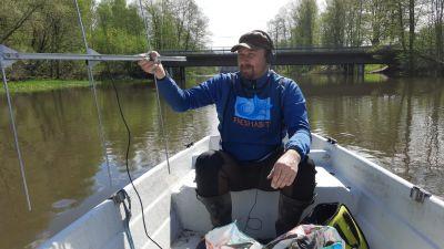 Juha-Pekka Vähä sitter i en båt och observerar fiskar med sändare i Svartån.