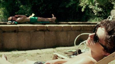 Elio (Timothée Chalamet) solar utomhus, i bakgrunden ser man Oliver (Armie Hammer) som också solar.