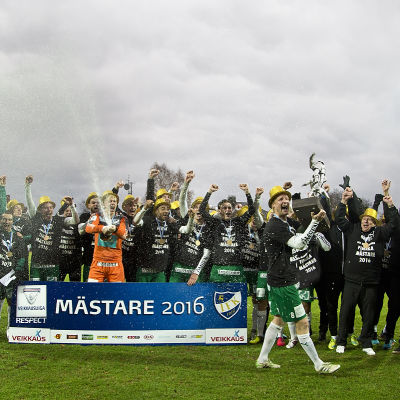 Jani Lyyski med mästarbucklan framför IFK Mariehamns spelare under guldfesten.