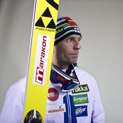 Janne Ahonen med skidorna i handen.