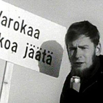 Yrjö Länsipuro Varokaa heikkoa jäätä -kyltin edessä.