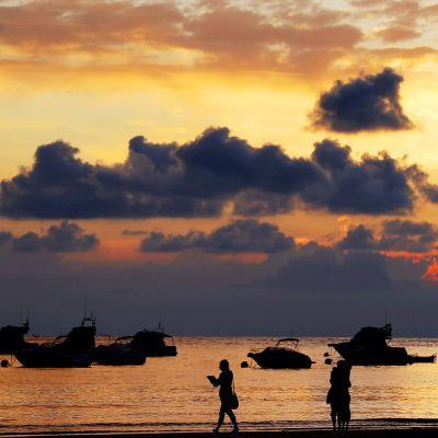 Ihmiset kävelevät espanajalaisella rannalla auringon laskiessa.