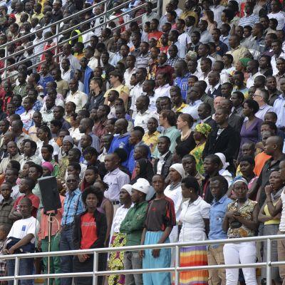 Ihmisiä seisoo vakavannäköisinä stadionin katsomossa.