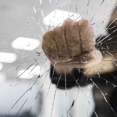 Nyrkki vasten rikkinäistä lasia.