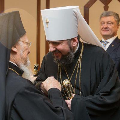 Kirkonmiehet kättelevät. Ukrainan presidentti hymyilee taustalla.