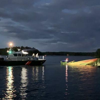 Sjöbevakningens båt belyser en motorbåt som delvis sjunkit på Erstan.