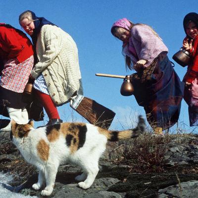 Noidiksi pukeutuneet tytöt leikkivät luudilla lentämistä, etualalla kissa.