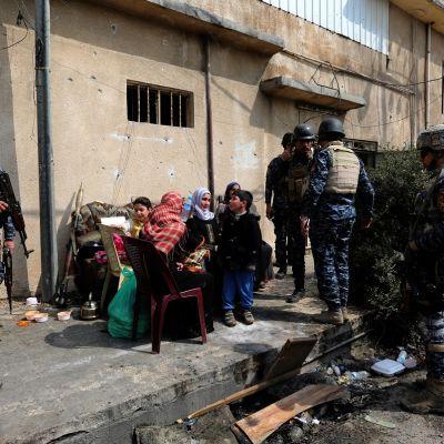 Ihmisiä istuu penkillä, Irakin poliiseja ympärillään.