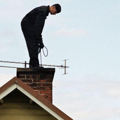 Nuohooja tekee työtään talon katolla