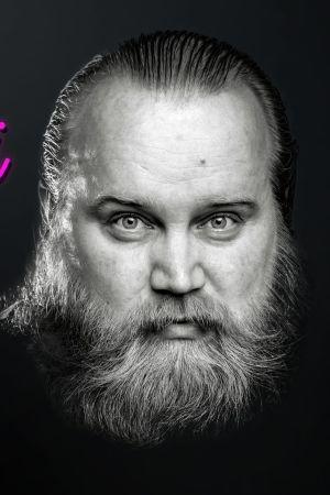 """Gösta Sundqvist katsoo kameraan mustavalkoisessa kuvassa. Kuvaan lisätty pinkillä neonvalolla teksti """"jaa muistosi Göstasta""""."""