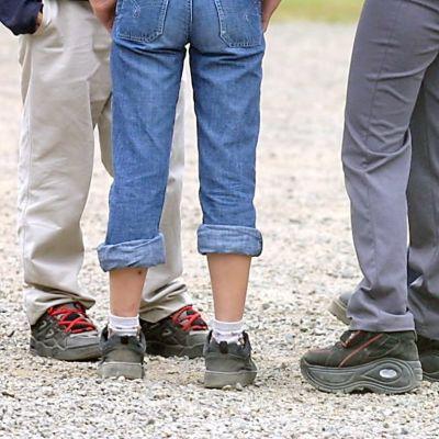 Närbild på fötter och ben av elever på en skolgård.