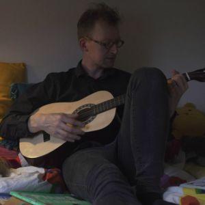 Man spelar gitarr för somnande barn