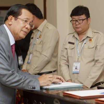 Hun Sen kansalliskokouksessa, kumartuu pöydän yli.