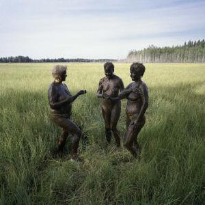 Tre kvinnor i lerpackning på en åker