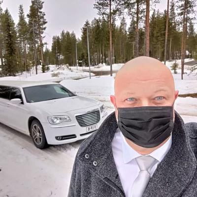 Harmaatakkinen mies musta maski kasvoillaan lumisessa metsämaisemassa, taustalla pitkä valkoinen limusiini.
