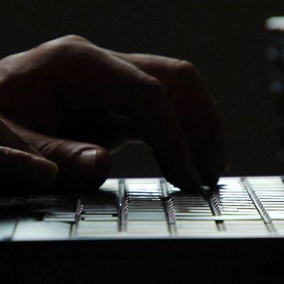 Kädet tietokoneen näppäimistöllä.