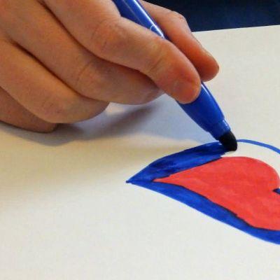 Kynä kädessä, joka piirtää sydämen