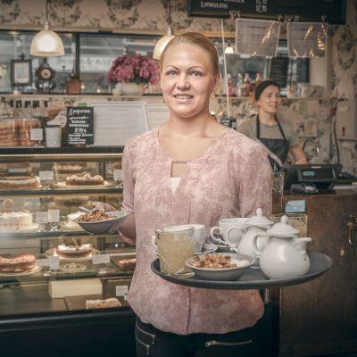 Miriam Laitinen tarjotin kädessään valmiina viemään tilaukset pöytään.