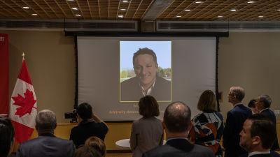 Bild av Michael Spavor visas på stor skärm.