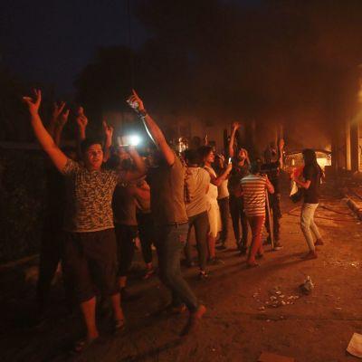 Mielenosoittajia kädet pystyssä ja palava rakennus