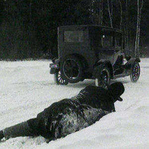 Muilutus: mies makaa hangessa, taustalla koppiauto