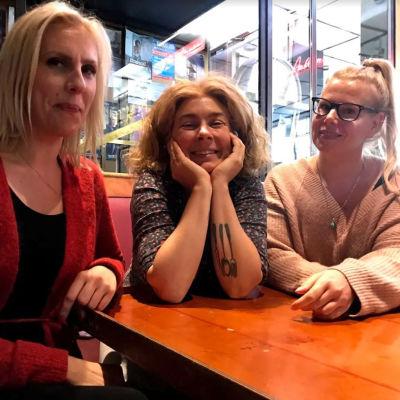 Maija Ilmoniemi,  Anikò Lehtinen ja Sofia Kilpikivi istuvat baarissa oluella.